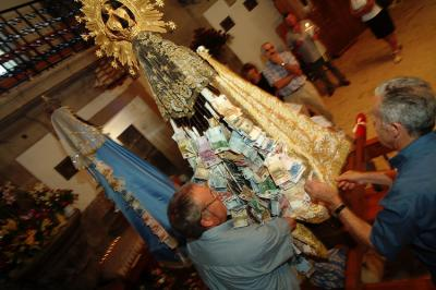 20080903012520-santa-miragres-con-billetes.jpg
